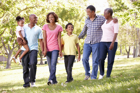 mixed race person: Multi-generation  family walking in park