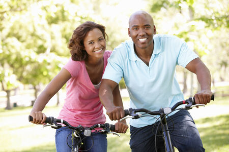 young couple smiling: Young  couple cycling in park