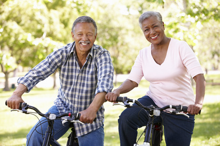 Senior  couple cycling in park Stock Photo - 33604819