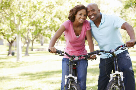 mid adult couple: Young  couple cycling in park