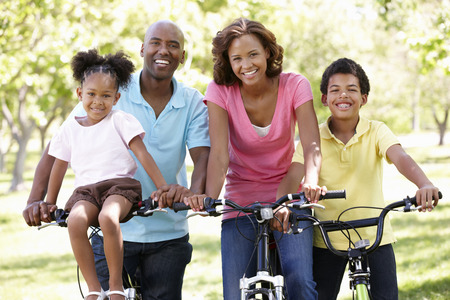 native american man: Family cycling in park Stock Photo