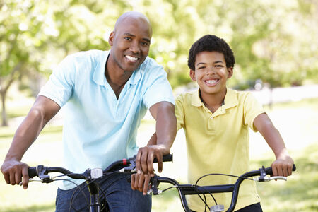 Father and son cycling in park photo
