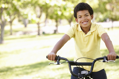 Boy cycling in park Stock Photo