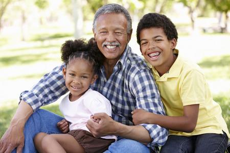 Grandfather and grandchildren in park Stock Photo