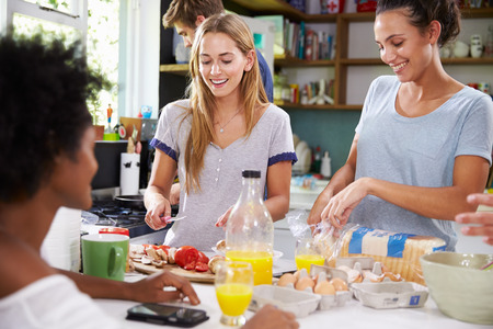 women friends: Group Of Friends Cooking Breakfast In Kitchen Together