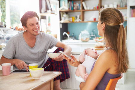 sitting at table: Family With Baby Girl Use Digital Devices At Breakfast Table Stock Photo