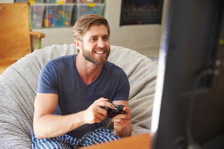 jugando videojuegos: Hombre en pijama Sentado En Silla Y Jugar videojuegos