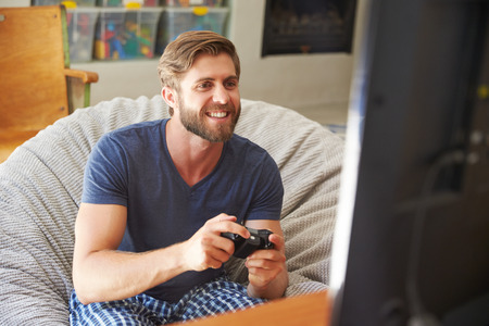 Man Wearing Pajamas Sitting In Chair And Playing Video Game