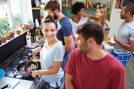 함께 부엌에서 아침을 요리하는 친구의 그룹 스톡 콘텐츠