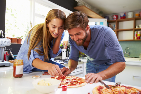 together standing: Young Couple Making Pizza In Kitchen Together