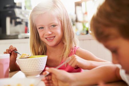 niños desayunando: Retrato de los niños que come el desayuno en el vector de cocina