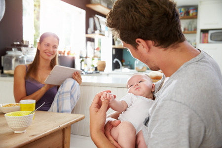 desayuno: Familia con la ni�a de Uso tableta digital en Mesa de desayuno Foto de archivo