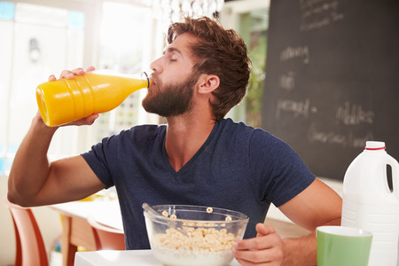 jugos: Hombre joven que come el desayuno y beber jugo de naranja