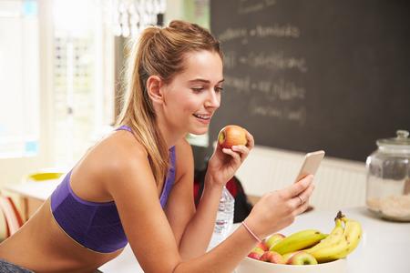 fitness: Frauen-tragende Gym Kleidung Blick in die Handy-