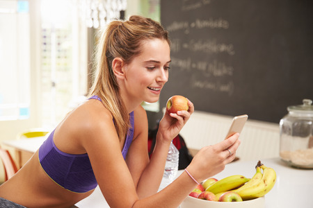 woman eating fruit: Woman Wearing Gym Clothing Looking At Mobile Phone