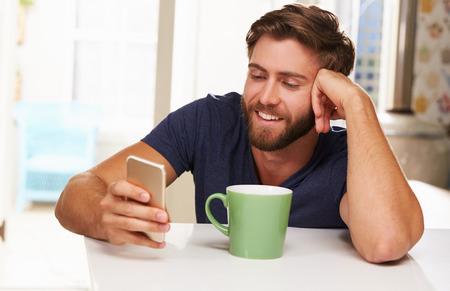tomando café: Hombre joven que bebe café y el uso de teléfono móvil en el hogar Foto de archivo