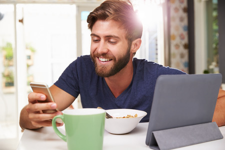 whilst: Man Eating Breakfast Whilst Using Digital Tablet And Phone Stock Photo