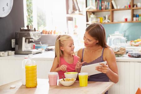 niños desayunando: Madre e hija que usa la tableta digital en el desayuno Mesa