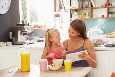 breakfast cereal: Mother And Daughter Using Digital Tablet At Breakfast Table