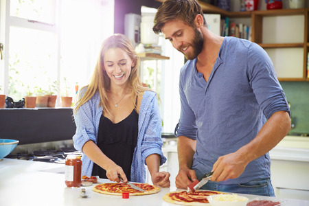 preparing food: Young Couple Making Pizza In Kitchen Together