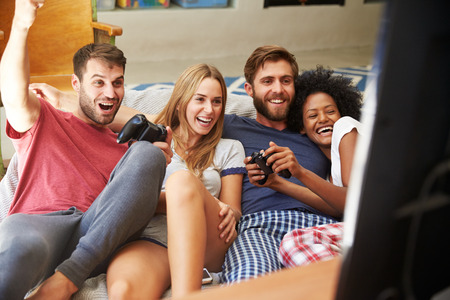 Group Of Friends Wearing Pajamas Playing Video Game Together photo