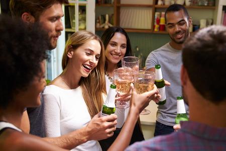 hombre tomando cerveza: Grupo de amigos que disfrutan Bebidas del partido en casa