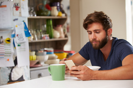 whilst: Man Eating Breakfast Whilst Using Mobile Phone