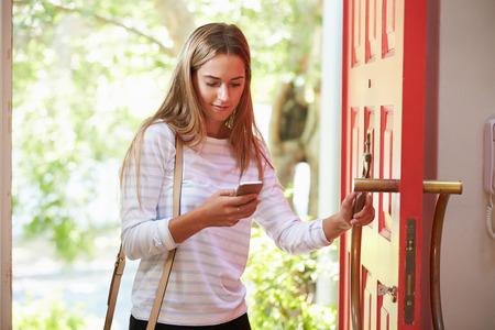 abriendo puerta: Mujer joven que vuelven a casa para el trabajo Mirando a Teléfono Móvil