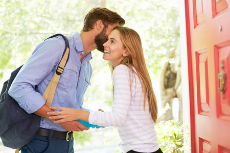 women kissing: Woman Saying Goodbye To Man Leaving Home With Packed Lunch Stock Photo