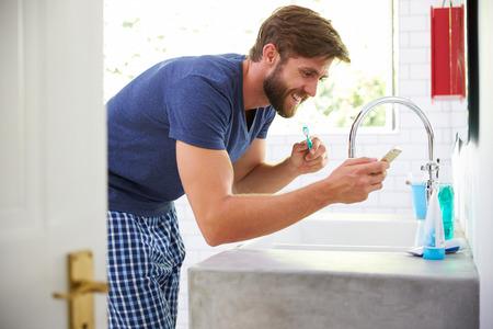 brushing: Man In Pajamas Brushing Teeth And Using Mobile Phone