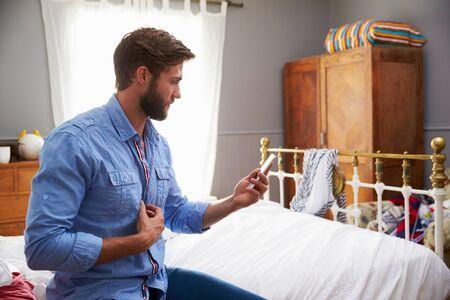 vistiendose: Hombre que se sienta en la cama que Vestirse Y Comprobación Teléfono Móvil Foto de archivo