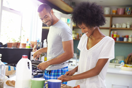 afroamericanas: Pares jovenes que preparan el desayuno en cocina Juntos
