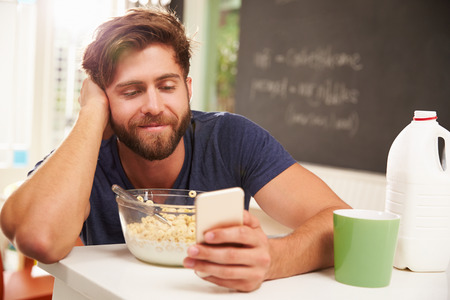 whilst: Young Man Eating Breakfast Whilst Using Mobile Phone Stock Photo