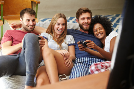 playing video game: Group Of Friends Wearing Pajamas Playing Video Game Together