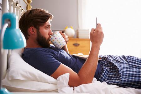 cama: El hombre que come el desayuno en la cama Mientras usa el teléfono móvil Foto de archivo