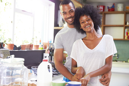 african man: Young Couple Preparing Breakfast In Kitchen Together Stock Photo