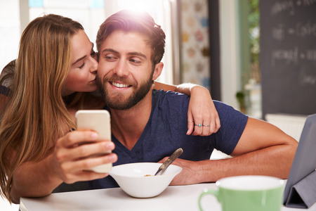 hot kiss: Couple Eating Breakfast Using Digital Tablet And Phone