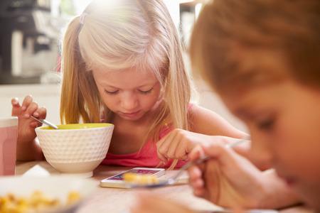 niños desayunando: Los niños que comen el desayuno, mientras que jugando con el teléfono móvil