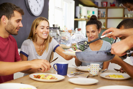 Group Of Friends Enjoying Breakfast In Kitchen Together photo