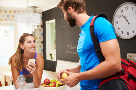 couple talking: Couple Wearing Gym Clothing Talking In Kitchen