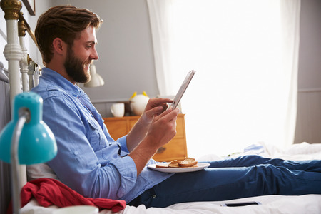 whilst: Man Eating Breakfast In Bed Whilst Using Digital Tablet