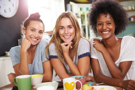 mujer tomando cafe: Tres amigos femeninos que gozan del desayuno en el país junto