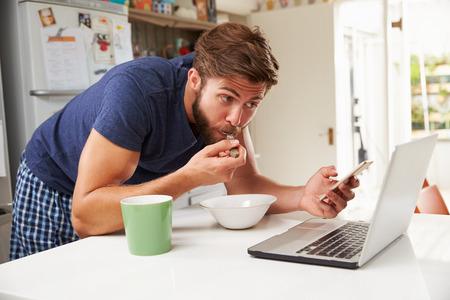 comiendo cereal: El hombre que come el desayuno Mientras que usa el teléfono móvil y la computadora portátil