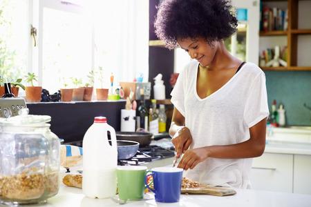 american food: Young Woman Wearing Pajamas Preparing Breakfast In Kitchen
