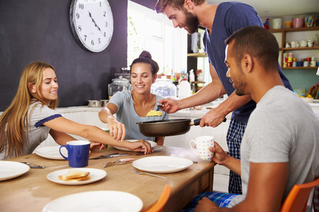 bacon love: Group Of Friends Enjoying Breakfast In Kitchen Together Stock Photo