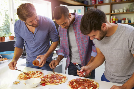 Three Male Friends Making Pizza In Kitchen Together Stock Photo