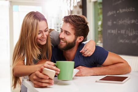 デジタル タブレットと電話を使用した朝食を食べるカップル