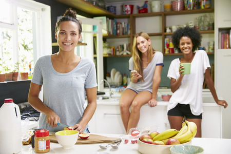Female Friends Making Breakfast Whilst Checking Mobile Phone photo