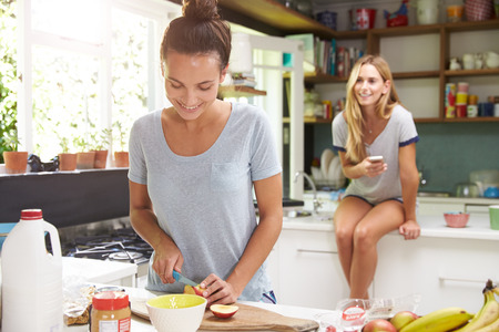 Two Female Friends Preparing Breakfast At Home Together Stock Photo