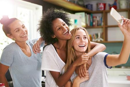 whilst: Three Female Friends Taking Selfie Whilst Making Breakfast
